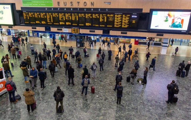 A sparse crowd watches departure boards at Euston Station in London
