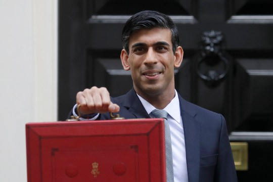Britain's Chancellor of the Exchequer Rishi Sunak stands outside No 11 Downing Street and holds up the traditional red box that contains the budget speech for the media, he will then leave to make budget speech to House of Commons, in London.