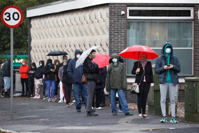 People stand in a queue to get tested for COVID-19 in Liverpool