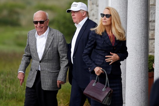 FILE PHOTO: Republican presidential candidate Donald Trump (C) speaks to media mogul Rupert Murdoch (L) and at his wife, former model Jerry Hall as they walk out of Trump International Golf Links in Aberdeen, Scotland, June 25, 2016. REUTERS/Carlo Allegri/File Photo