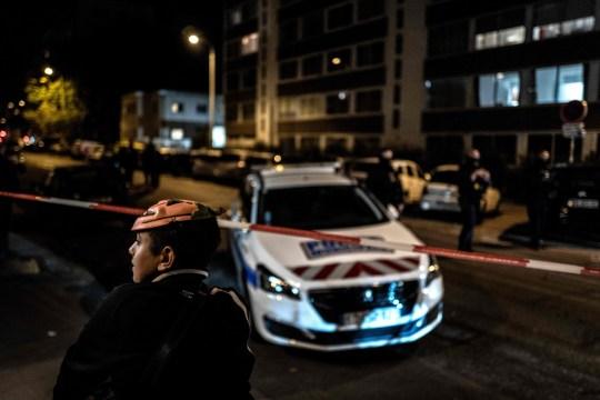 Un garçon portant un masque d'Halloween détourne le regard au premier plan alors que des soldats français et des agents de la police municipale se tiennent derrière une zone de bouclage près de l'église orthodoxe où un assaillant armé d'un fusil à canon tronqué a blessé un prêtre orthodoxe lors d'une fusillade avant de s'enfuir, en octobre. 31 janvier 2020 à Lyon.