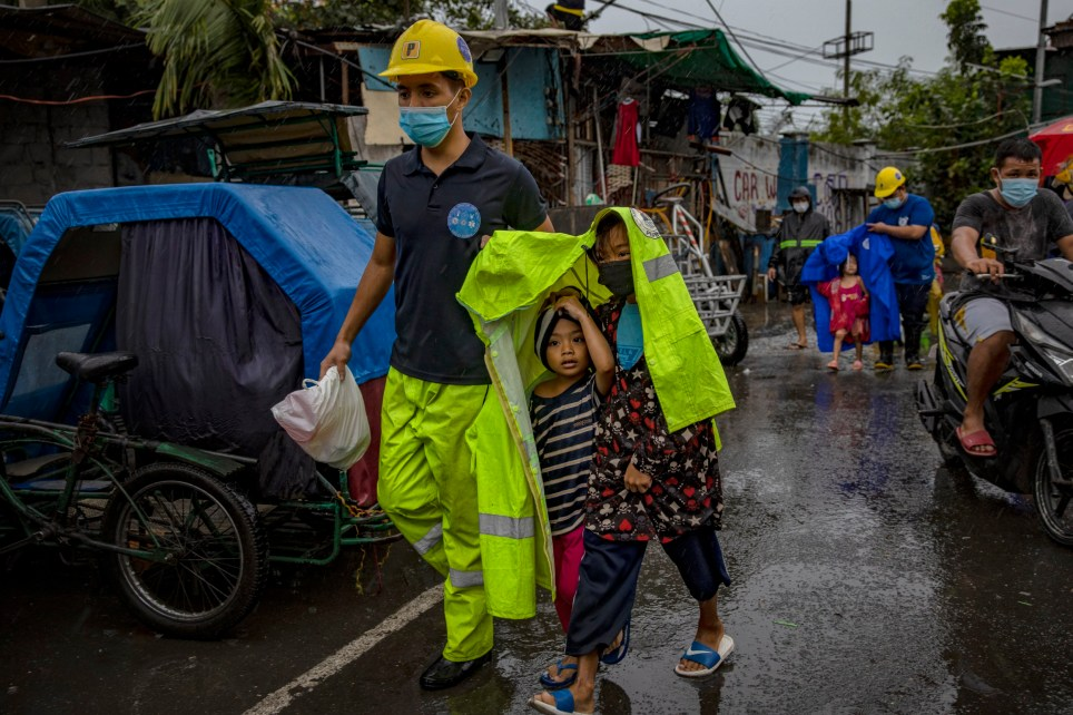 MANILA, PHILIPPINES - NOVEMBER 01: A rescue worker covers children in a raincoat as they evacuate before Typhoon Goni hits on November 1, 2020 in Manila, Philippines. Super Typhoon Goni, this year's most powerful storm in the world, has made landfall in the Philippines with wind gusts of up to 165 miles per hour early Sunday. At least two people have been killed so far and hundreds of thousands have been evacuated ahead of the storm. (Photo by Ezra Acayan/Getty Images) *** BESTPIX ***