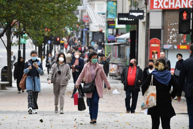 Pedestrians, some wearing masks because of the coronavirus pandemic, walk in the street in central London on November 1, 2020 as England prepares to enter into a second lockdown in an effort to stem soaring infections. - A new four-week coronavirus lockdown in England will be extended if it fails to reduce infection rates, the government said Sunday, as it faced criticism over the abrupt decision to shut down again. The second national lockdown, hastily announced late Saturday following warnings hospitals could become overwhelmed within weeks, is set to come into force from Thursday and end on December 2. (Photo by JUSTIN TALLIS / AFP) (Photo by JUSTIN TALLIS/AFP via Getty Images)