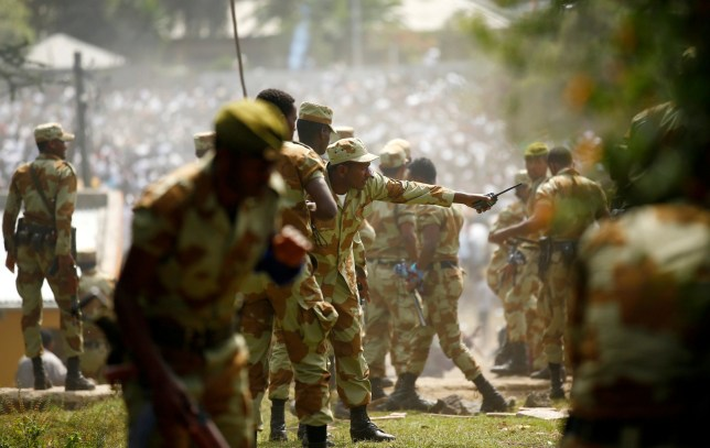 Security personnel attempt to stop protesters during the Irrechaa, the thanks giving festival of the Oromo people in Bishoftu town of Oromia region, Ethiopia, October 2, 2016. REUTERS/Tiksa Negeri - S1BEUEQRLCAB