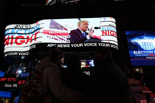 NEW YORK, USA - NOVEMBER 3: People watch election results on a giant screen at Times Square is seen on the 2020 United States Presidential Election night in New York City, United States on November 3, 2020. (Photo by Tayfun Coskun/Anadolu Agency via Getty Images)