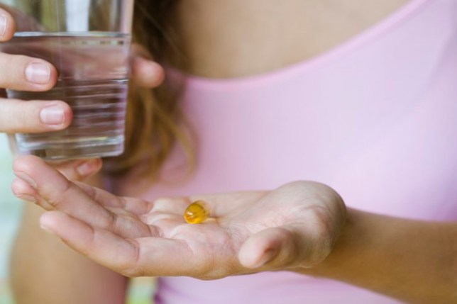 Woman holds supplement in one hand and glass of water in the other