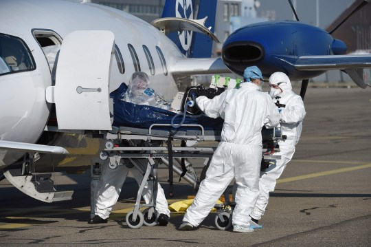 Medical staff take care of a patient infected with the Covid-19 disease upon his arrival by plane from the Lyon's area on November 6, 2020, at Strasbourg airport, eastern France, as France is facing a second wave of the covid-19 pandemic caused by the novel coronavirus.