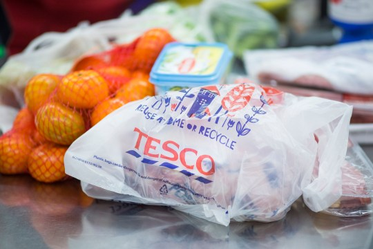 A Tesco-branded plastic shopping bag sits on a check-out desk inside a Tesco supermarket