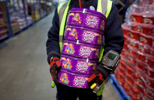 An employee carries tins of Quality Street