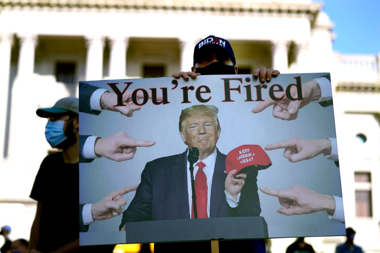 A supporter of President-elect Joe Biden holds a sign referring to President Donald Trump outside the Pennsylvania State Capitol, Saturday, Nov. 7, 2020, in Harrisburg, Pa., after Biden defeated Trump to become 46th president of the United States. (AP Photo/Julio Cortez)
