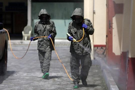 epa08809078 Des policiers de l'unité spéciale de police (BRIMOB) pulvérisent du liquide désinfectant dans une église catholique pour empêcher la propagation du coronavirus à Banda Aceh, Indonésie, le 9 novembre 2020. EPA / HOTLI SIMANJUNTAK