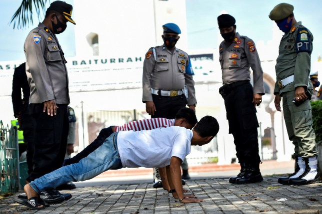 Members of the public perform push-ups as punishment for not wearing face masks amid the Covid-19 coronavirus pandemic in Banda Aceh on November 10, 2020. (Photo by CHAIDEER MAHYUDDIN / AFP) (Photo by CHAIDEER MAHYUDDIN/AFP via Getty Images)