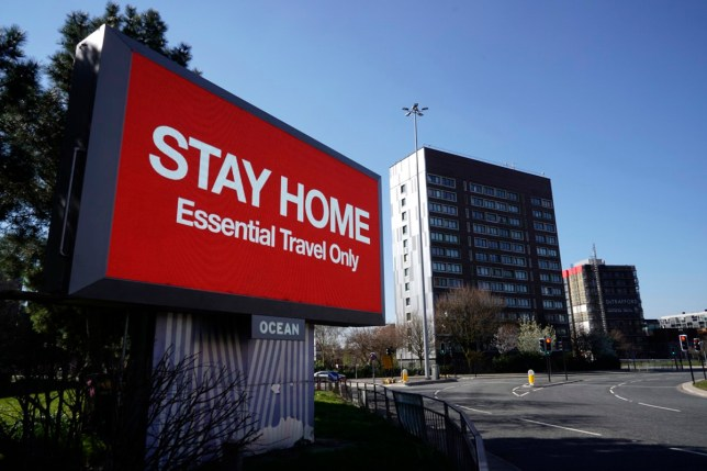 a giant sign over a motorway in manchester urging people to stay at home