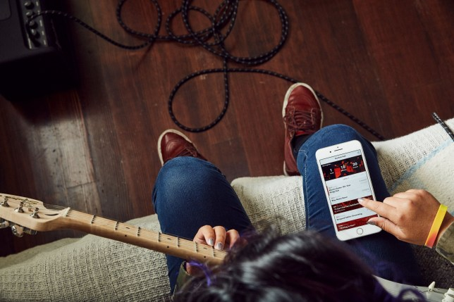A man holding a guitar while using the Fender Play app