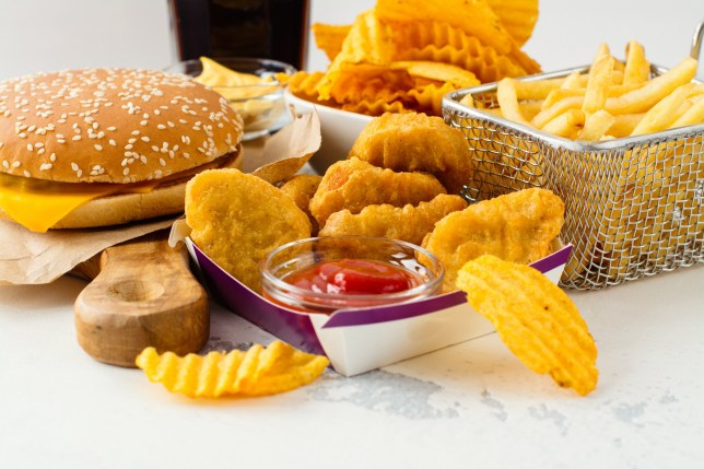 Junk food on white table. Fast carbohydrates not good for health, heart and skin