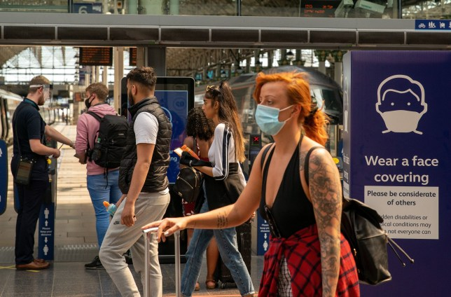 Commuters wearing protective face masks walk along a concourse at Manchester Piccadilly railway station