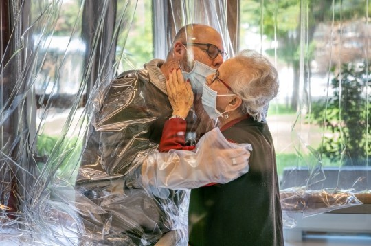 Resident kisses a relative through a plastic sheet installed in a special 'hug room' organised to keep both parties safe from novel coronavirus infection, at a care home in Castelfranco Veneto, Italy, in this handout photo released on November 11, 2020. Centro residenziale per anziani Domenico Sartor/Handout via REUTERS ATTENTION EDITORS THIS IMAGE HAS BEEN SUPPLIED BY A THIRD PARTY.
