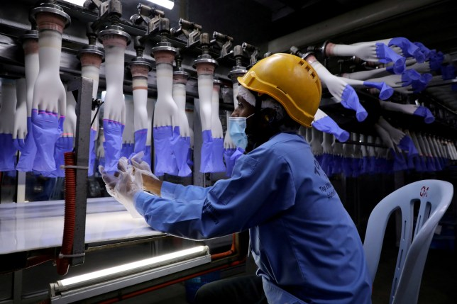 A worker inspects newly-made gloves at Top Glove factory in Shah Alam, Malaysia August 26, 2020.