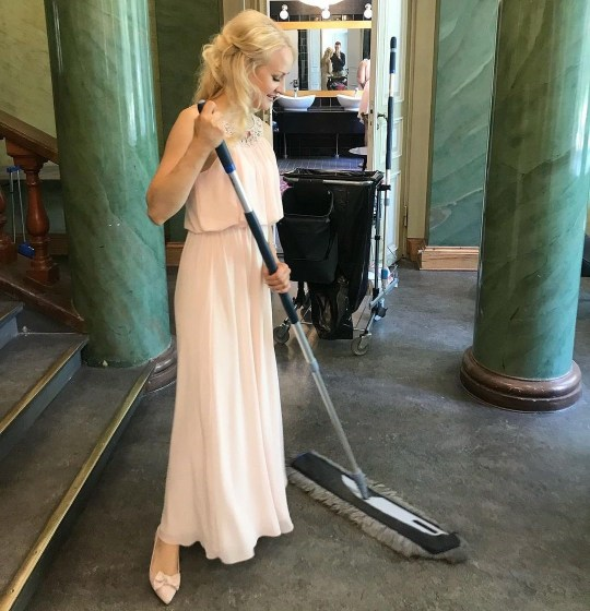 Woman mopping hotel in white dress