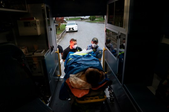 GLEN BURNIE, MD - NOVEMBER 11: (EDITORIAL USE ONLY) Firefighters and paramedics with Anne Arundel County Fire Department load a patient into an ambulance while responding to a 911 emergency call on November 11, 2020 in Glen Burnie, Maryland. Maryland Governor Larry Hogan announced yesterday that he will reimpose statewide restrictions for the first time since the start of the pandemic as COVID-19 cases reached record highs in the state for the eighth day in a row. (Photo by Alex Edelman/Getty Images)