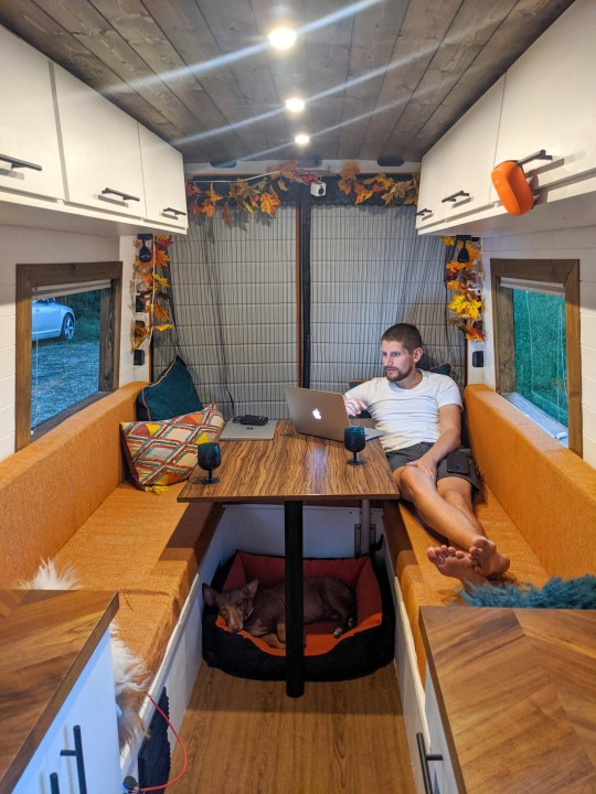 james sitting and working in the camper van