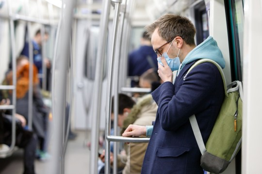 Ill man in glasses feeling sick, coughing, wearing protective mask against transmissible infectious diseases and as protection against the flu in public transport. New coronavirus 2019-nCoV from China; Shutterstock ID 1355109323; Purchase Order: -