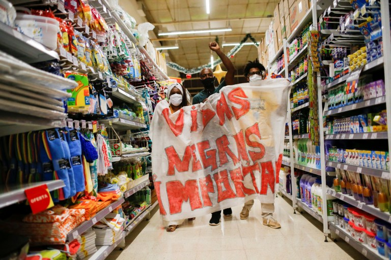 Les manifestants se tiennent entre les allées des supermarchés tenant un panneau de protestation blanc et rouge