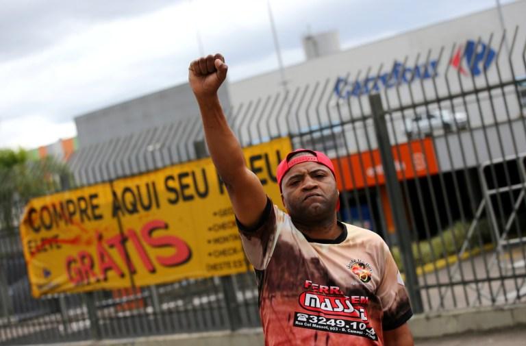Un homme noir se tient devant un supermarché avec son poing levé en signe de protestation