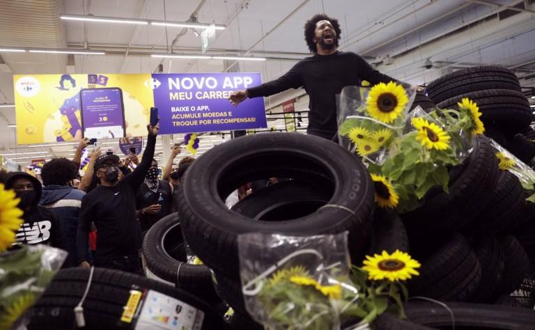 Un homme se tient à l'intérieur d'un supermarché au milieu d'un tas de pneus et de tournesols