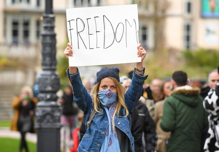 Anti-lockdown protester holds up sign of freedom