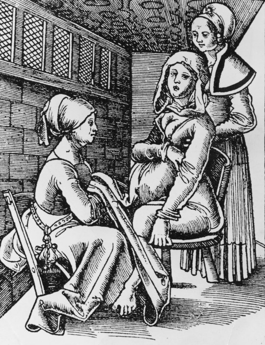 A woman being helped to give birth on a birth chair, by two midwives, circa 1513