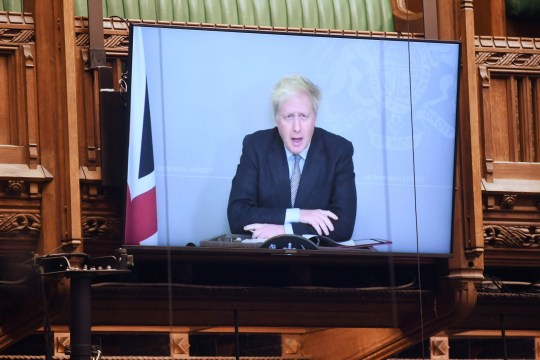 A handout photograph released by the UK Parliament shows a screen displaying Britain's Prime Minister Boris Johnson as he takes part remotely via a video call in the weekly Prime Minister's Questions (PMQs) during a hybrid, socially distanced session at the House of Commons in London on November 25, 2020. - Britain's government on Wednesday unveiled plans to slash the foreign aid budget to help mend its coronavirus-battered finances, prompting one minister to quit and defying impassioned calls to protect the world's poorest people. Johnson has been forced into self-isolation after meeting with one of his MPs who consequently tested positive for coronavirus. (Photo by JESSICA TAYLOR / various sources / AFP) / RESTRICTED TO EDITORIAL USE - MANDATORY CREDIT