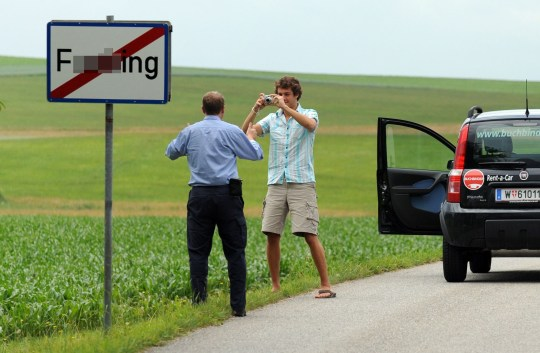 (FILES) This file photo taken on June 18, 2008 shows tourists taking pictures of the road sign of the village of Fucking, some 35 km North of Salzburg, Austria. - Residents of an Austrian village will ring in the new year 2021 under a new name -- Fugging -- after ridicule, especially on social media, became too much to bear. They finally grew weary of Fucking. (Photo by Mladen ANTONOV / AFP) (Photo by MLADEN ANTONOV/AFP via Getty Images)