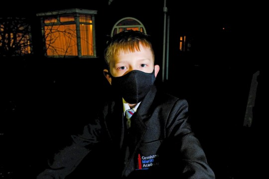 Jermaine Welsh, 12, wearing the black face mask with a small white logo to Ormiston Maritime Academy for three weeks before being told it was unsuitable.