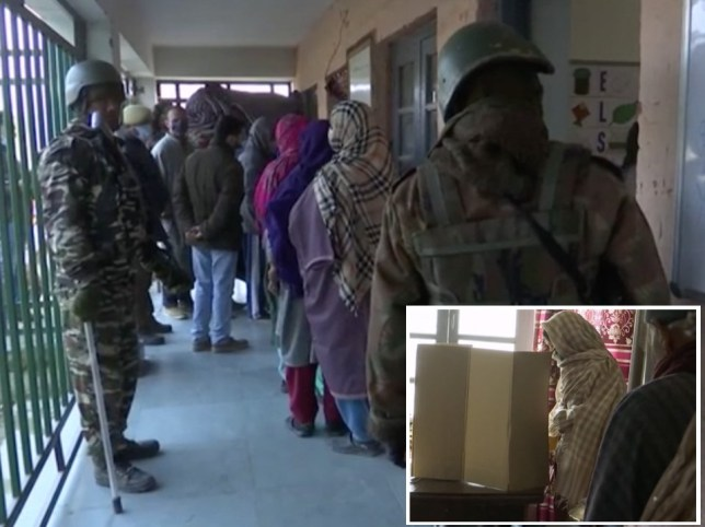 Armed soldiers stand guard as men and women line up inside a building