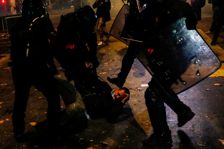 A demonstrator is arrested and draged on the ground by a group of French anti-riot police