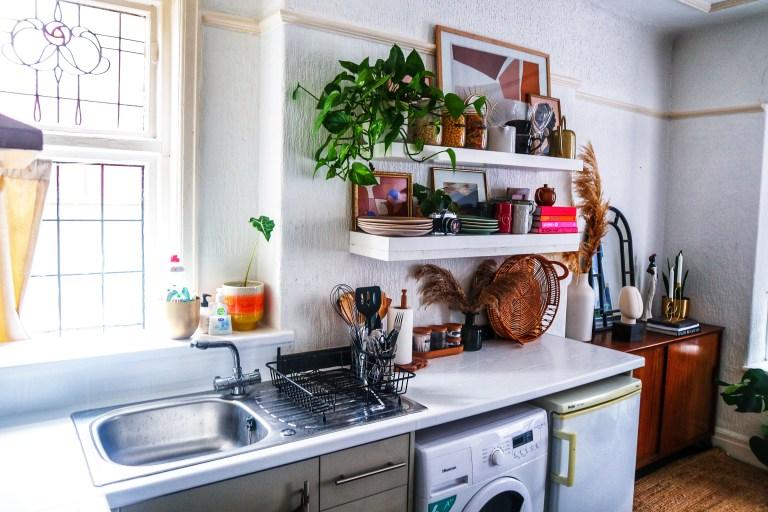 shelves above small fridge and washing machine, plus sink
