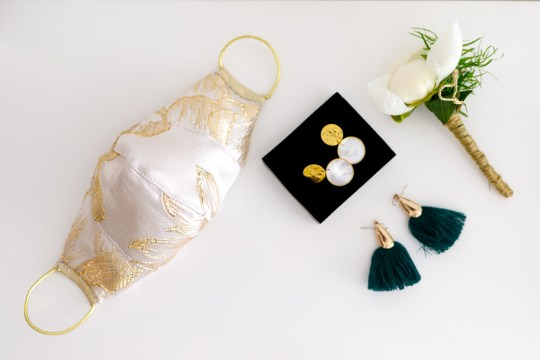 a wedding face mask laid out next to earrings and a flower