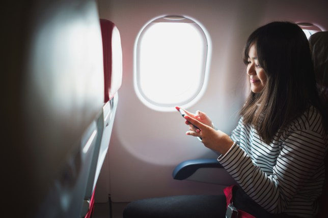 Young asian girl using smart phone on commercial flight