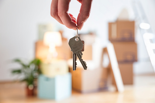 woman holding house key in new home