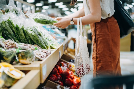 Cropped shot of young woman shopping for fresh organic groceries in supermarket.