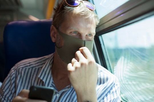 A man wearing a face mask on the train