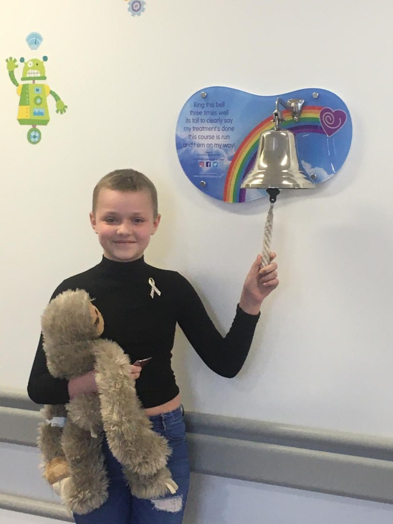 Grace ringing the bell on a children's cancer ward to signal she was free from cancer