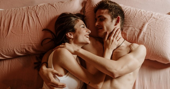 A couple in bed together on pink sheets