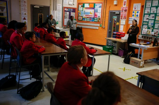 A teacher explains social distancing measures to a group of year 7 students in a classroom at City of London Academy Highgate Hill on September 4, 2020 in London, England.