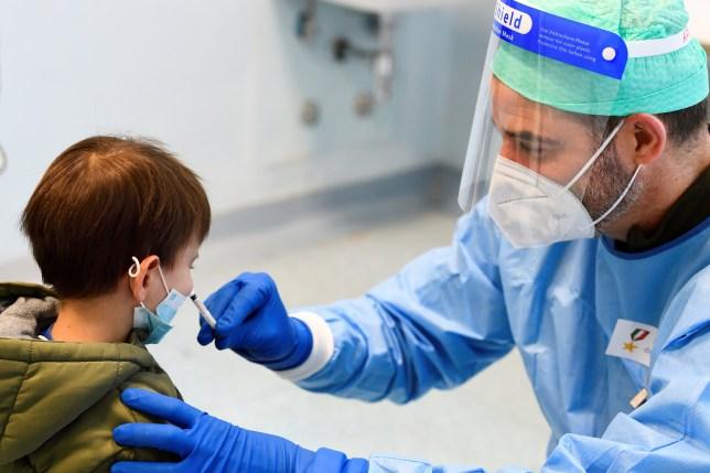 Un médecin militaire administre un vaccin antigrippal à un enfant dans un hôpital militaire après que les autorités sanitaires ont conseillé aux gens de se faire vacciner contre la grippe pour éviter toute confusion avec les symptômes de la maladie à coronavirus, à Milan, en Italie, le 20 novembre 2020.