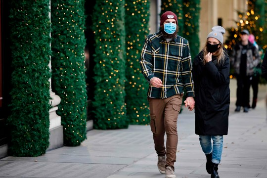 Pedestrians wearing a masks because of the novel coronavirus pandemic walk past a store front covered in Christmas decorations in central London on November 27, 2020,