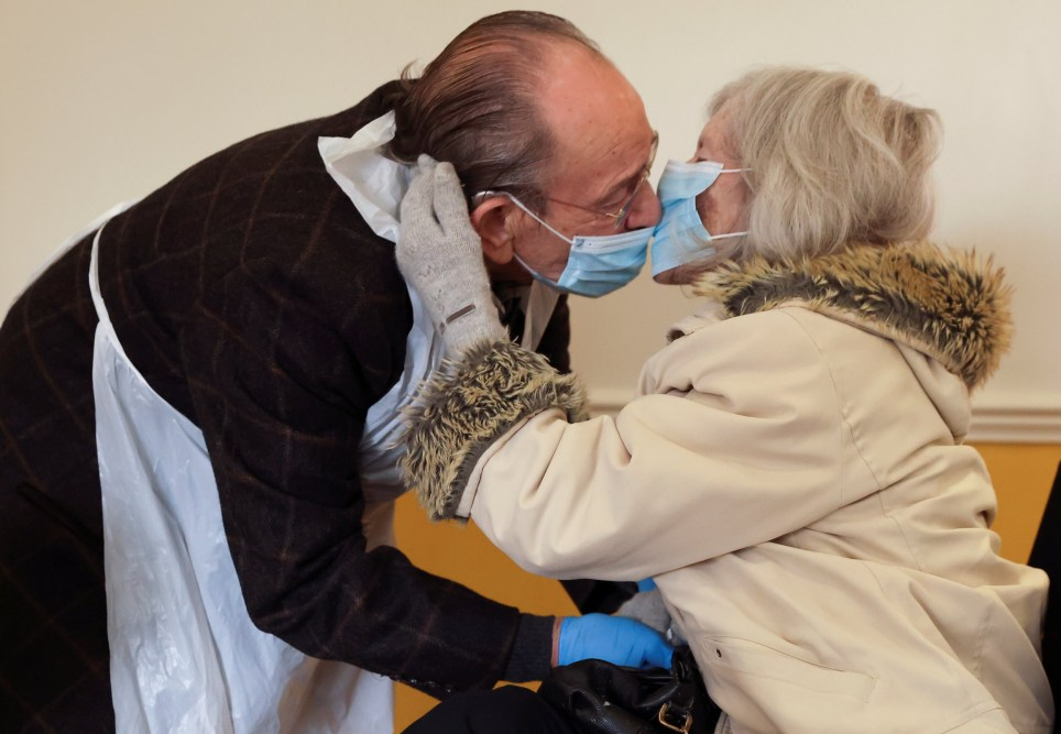 Bob Underhill, 84, and his wife Patricia, 82, suffering from Alzheimer's, kiss through a face mask as they are allowed to visit with physical contact for the first time at The Chiswick Nursing Centre, which has introduced a coronavirus disease (COVID-19) test with results ready in thirty minutes, in London, Britain December 2, 2020.