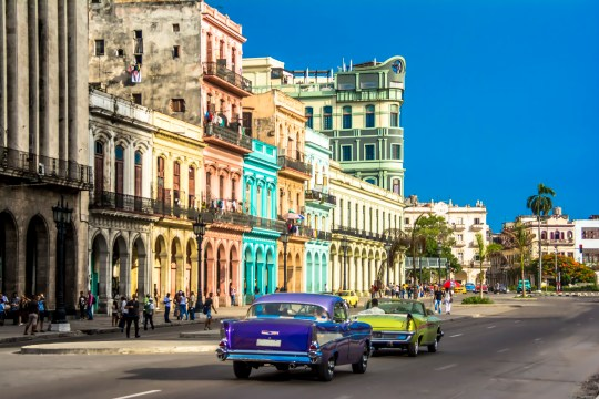 View of downtown Havana city with old classic cars and people walking on the street, Cuba.