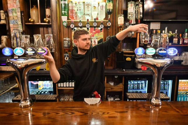 David Morgan, supervisor at The Borough pub in Cardiff, puts glasses on top of the beer taps ahead of closing for two weeks as pubs, bars, restaurants and cafes are forced to stop selling alcohol and shut by 6pm as part of a new round of coronavirus restrictions that come into force in Wales on Friday night. PA Photo. Picture date: Friday December 4, 2020. See PA story HEALTH Coronavirus Wales. Photo credit should read: Ben Birchall/PA Wire